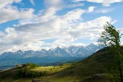 在山之间的美丽的晴朗的谷与豪华的云彩 免版税图库摄影