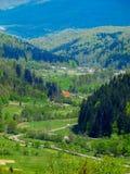 在山之间的路,在距离卡车和房子 免版税库存照片