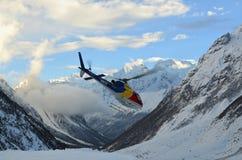 在山之间的飞行直升机在喜马拉雅山 库存图片
