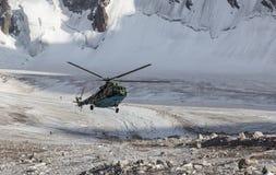 在山冰的军事直升机着陆galcier在紧急情况 免版税库存照片