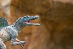 在山前面的灰色spinosaurus玩具 免版税图库摄影