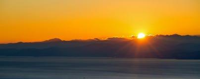 在山后的太阳设置在海岸和城市的云彩 图库摄影
