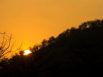 在山后的太阳设置 库存照片