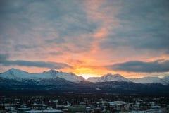 在山后的明亮的日出在一个多云冬日 免版税库存照片