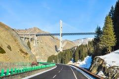 在山和一座吊桥的高速公路在它 免版税库存照片
