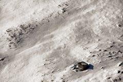在山和一间小的客舱的雪 图库摄影