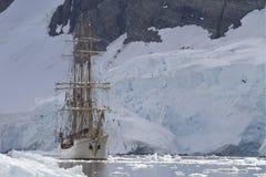 在山和冰川o背景的旅游帆船  免版税库存照片