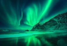 在山和冷淡的海滨上的绿色极光borealis 库存图片