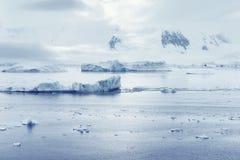 在山和大块的低云冰漂浮口岸Lockroy研究工作站 免版税库存图片