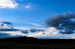 在山和平地剪影的剧烈的skyscape有形成在非常蓝天的stormclouds的在黄昏附近 JPG 免版税库存照片