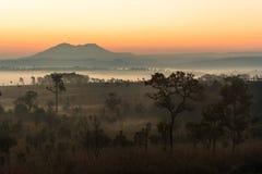 在山和有薄雾的森林上的日出在早晨 库存照片