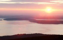 在山和海岸的桃红色日出 图库摄影