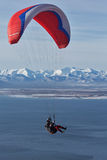 在山和海背景的滑翔伞飞行  库存图片