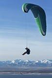 在山和海背景的滑翔伞飞行  免版税库存图片