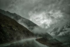 在山和湿柏油路的低云 库存图片