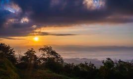 在山地形的日出在薄雾海,在多云天空 义卖市场 免版税图库摄影