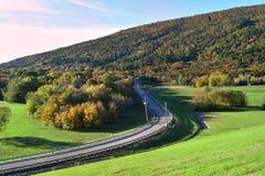 在山坡的弯曲的路与被盖的绿色被归档的和秋叶 免版税库存图片