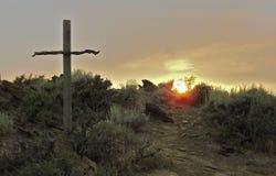 在山坡的木十字架在黎明 免版税库存图片