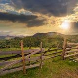 在山坡草甸的篱芭在日落的山的 库存图片