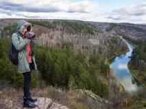在山壁架边缘的一个女孩拍摄河的一个美好的轮 免版税库存图片