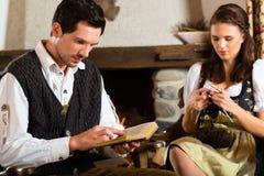 在山小屋的年轻夫妇在火地方 免版税库存照片