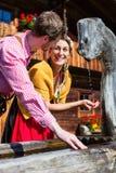 在山小屋饮用水的夫妇从来源 图库摄影
