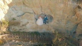 在山小山的倾斜的婚姻的夫妇立场 r 免版税库存照片