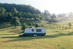 在山小山的边的拖车在草的 免版税图库摄影