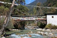 在山小河的祷告旗子装饰的桥梁在不丹 库存图片