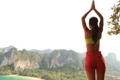 在山峰峭壁的健康妇女实践瑜伽 库存图片
