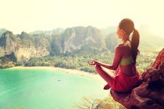 在山峰峭壁的健康妇女实践瑜伽 免版税库存图片