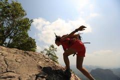 在山峰峭壁的妇女远足者上升的岩石 库存图片