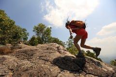在山峰峭壁的妇女远足者上升的岩石 免版税图库摄影