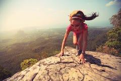 在山峰峭壁的妇女远足者上升的岩石 图库摄影