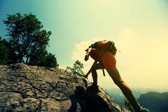 在山峰峭壁的妇女远足者上升的岩石 免版税库存照片