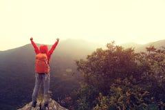 在山峰峭壁的妇女远足者开放胳膊 免版税库存图片