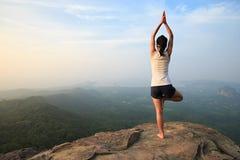 在山峰峭壁边缘的年轻健身妇女实践瑜伽 库存图片