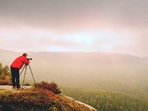 在山峰的专业摄影师工作 自然摄影师拍与镜子照相机的照片在岩石 免版税库存图片
