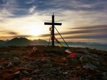在山峰的大木十字架在与佛教祈祷的旗子的风 在阿尔卑斯峰顶顶部的十字架 免版税库存照片