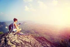 在山峰的妇女远足者用途数字式片剂 免版税图库摄影