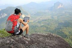 在山峰的妇女远足者用途数字式片剂 库存图片