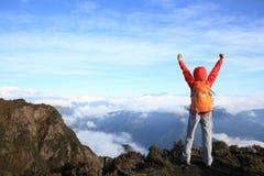 在山峰的少妇远足者开放胳膊 免版税图库摄影