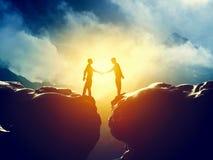 在山悬崖的两个人握手 事务 免版税库存照片
