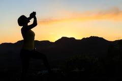 在山日落的妇女上升的成功剪影 免版税库存图片