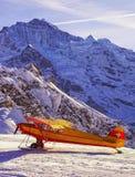 在山机场的黄色红色飞机在峰顶前面我 图库摄影