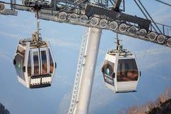 在山森林背景关闭的两间空中览绳滑雪电缆车客舱看法 库存照片