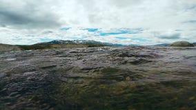 在山河小河赛跑的透明的饮用水 流动在小卵石和岩石下的冷的河小河 股票录像