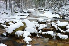 在山河的冬天 在用新鲜的粉末雪和懒惰水盖的小河的大石头与低级 免版税图库摄影