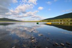 在山湖的木小船 免版税库存照片