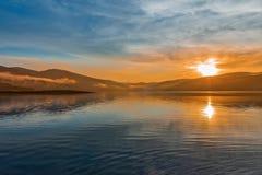 在山湖的橙色日落 库存照片